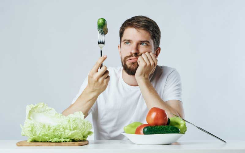 a man looking at a cucumber on a fork