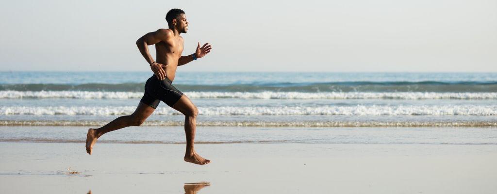 man running barefoot on sand