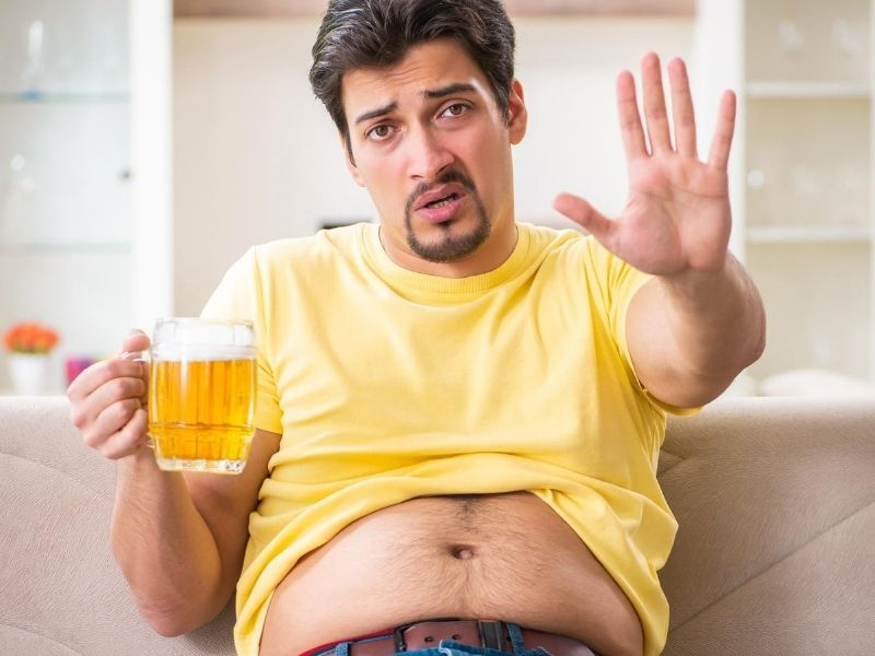 guy holding beer with big belly saying wait
