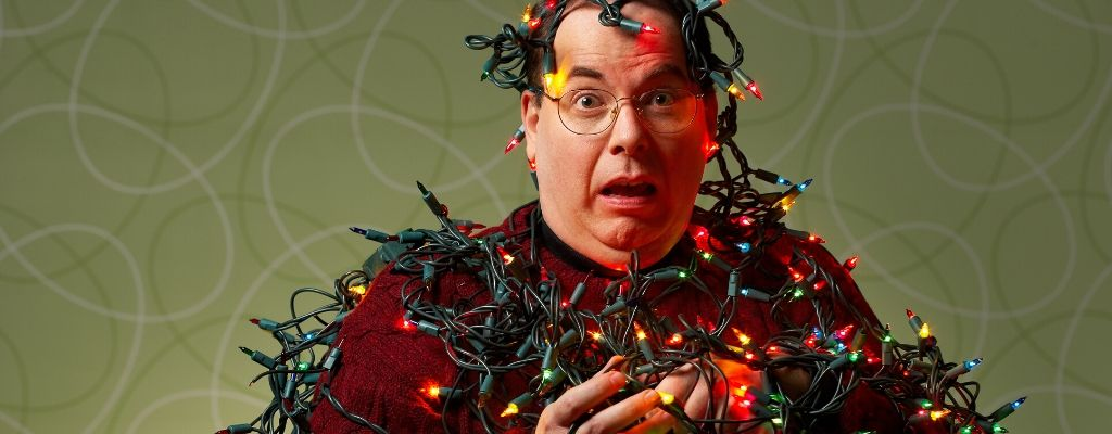 man wrapped in christmas lights