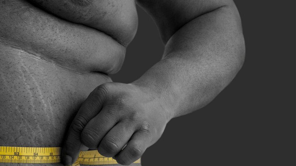 man measuring belly fat
