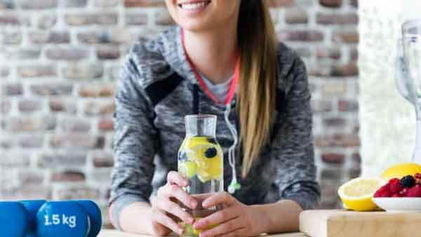woman showing a glass of lemon water