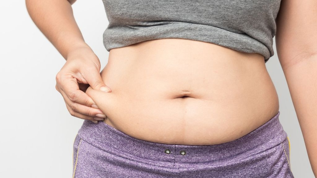 woman pinching side belly fat